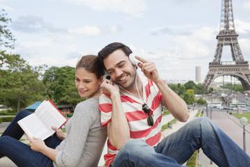 Frankreich, Paris, Porträt eines Paares mit Reiseführer und Kopfhörern vor Eiffelturm
