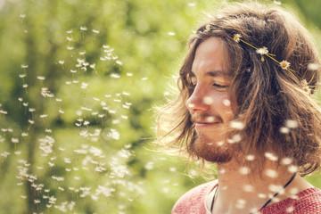 Lächelnder junger Mann mit Pusteblume