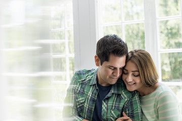 Couple embracing by a window.
