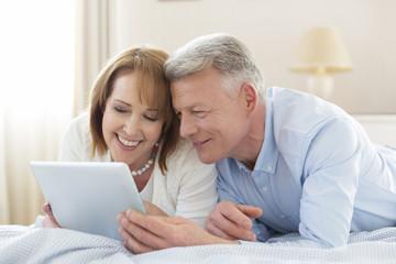 Älteres Paar, Entspannung auf dem Bett mit Tablet-PC