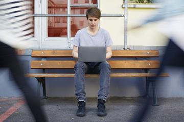 Man sitzt am Tisch mit Laptop