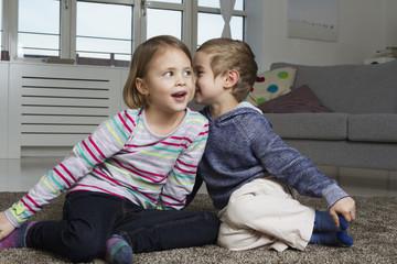 Bruder und Schwester flüstern auf Teppich im Wohnzimmer