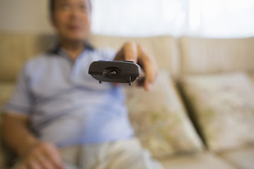 Man sitting on sofa holding remote control.