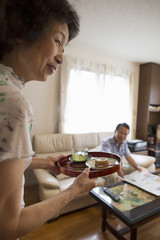 A woman serving a tray of food to a man sitting on a sofa.