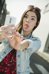 Junge Frau, die ein Selfie im Freien macht