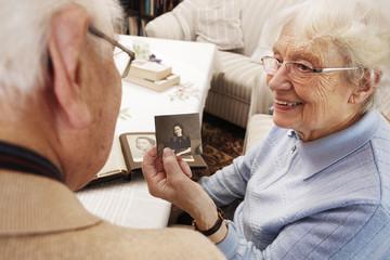 Seniorin, Frau zeigt Ehemann altes Foto von sich selbst