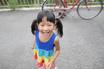 A young girl with pigtails smiling at the camera.