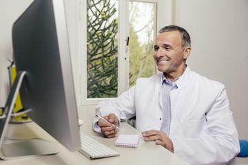 Lächelnder Arzt sitzt am Schreibtisch mit Computer vor sich