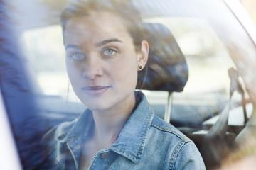 Porträt der jungen Frau auf Rücksitz eines Autos