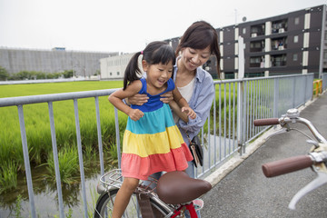 A mother lifting her daughter onto a bicycle.