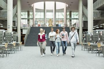 Gruppe von Studenten zu Fuß in einer Universitätsbibliothek