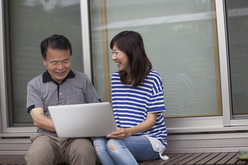 A man and a women sitting outside a house. Holding a laptop computer.