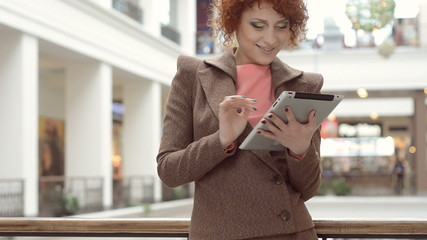 Redhead business woman he uses on the tablet and smiling