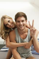 Lachendes junges Paar sitzt auf dem Bett