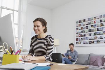 Frau zu Hause, sitzend am Schreibtisch mit Computer, Mann im Hintergrund