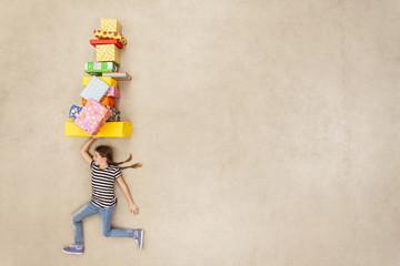 Mädchen balanciert Stapel von Geschenken