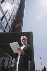 Geschäftsfrau außerhalb des Gebäude mit Tablet-PC