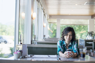 A woman in a checked shirt sitting at a table, laughing and looking at her smart phone.