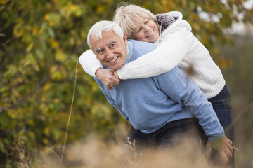 Senior nimmt seine Frau ein Huckepack