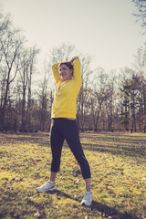 Frau macht Sport im Wald, Dehnen