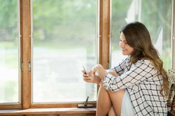 A woman sitting by a window, looking at her cell phone.
