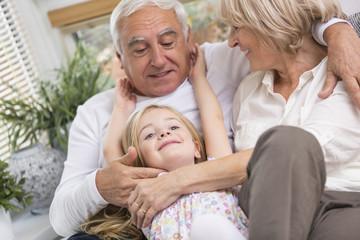 Paar und Enkelin entspannt auf dem Sofa im Wohnzimmer