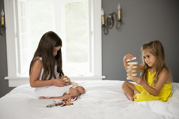 Two girls sitting on a bed playing together.