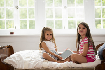 Two girls sitting holding a digital tablet.