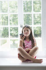 A girl sitting playing, holding a smart phone.