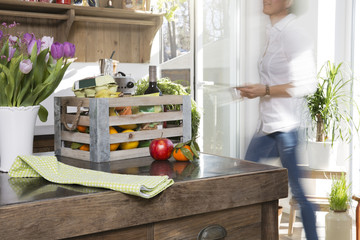 Frau in der Küche mit Kiste Lebensmittel