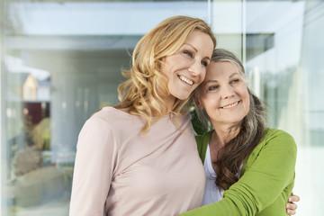 Mutter und ihre Tochter Seite an Seite vor ihrem Haus