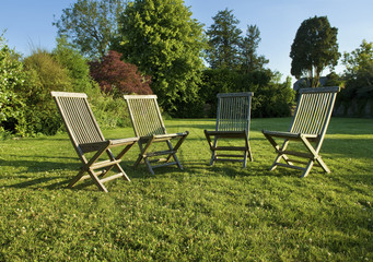 Garden chairs placed grouped on a lawn in Gloucestershire in summer.
