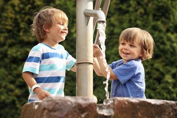 Zwei kleine Jungen spielt mit Wasserpumpe
