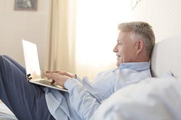 Lächelnder Mann liegt auf dem Bett mit seinem Laptop