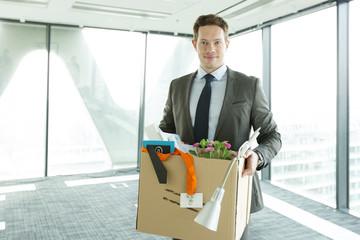Geschäftsman,n Karton ins Büro tragen