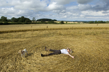 A farmer lying on his back in the stubble creating a pattern