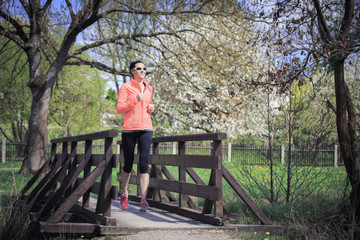 Frau beim Joggen über eine Fußgängerbrücke