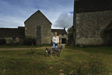 A woman standing in shadow in a farmyard with two large lurcher dogs.