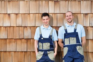 Zwei Handwerker an Holzwand