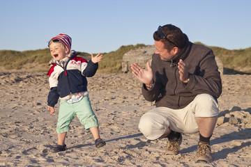 Dänemark, Blåvand, kleines Mädchen und ihr Vater am Strand