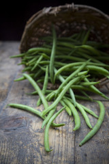 Grüne Bohnen und Korb auf Holztisch