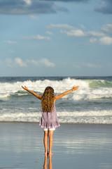 Australien, New South Wales, Pottsville, Mädchen mit langen Haaren am Meer mit ausgestreckten Armen