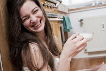 Lächelnde junge Frau Frau mit Tasse Tee zu Hause