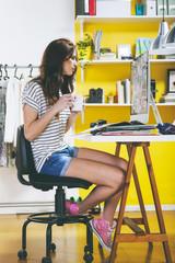 Weibliche Mode-Blogger mit Kaffeetasse, Blick auf Computer in ihrem Büro