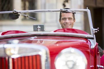 Porträt eines Mannes mit seinem roten Oldtimer