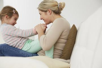 Deutschland, München, Mutter und Tochter sitzen auf dem Sofa, herumalbern