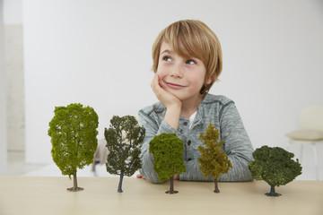 Deutschland, Junge sitzt am Tisch mit Baummodellen, Umweltschutz