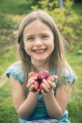Lächelndes kleines Mädchen, die Hand voll Erdbeeren