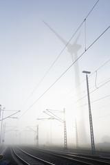 Deutschland, Hamburg, Windkraftanlage neben Bahnstrecke im Frühnebel