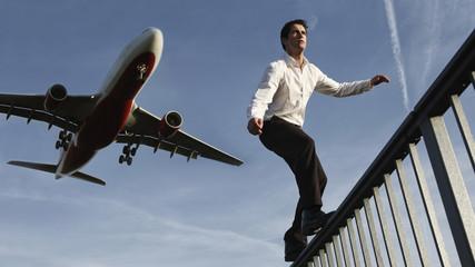 Mann mit Flugzeug im Hintergrund, Balancieren auf Geländer
